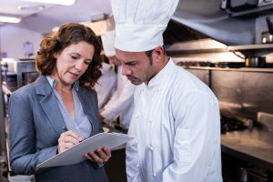 QC at restaurant kitchen standing with chef - Value of Sanitation Certification of Food Equipment | NSF International